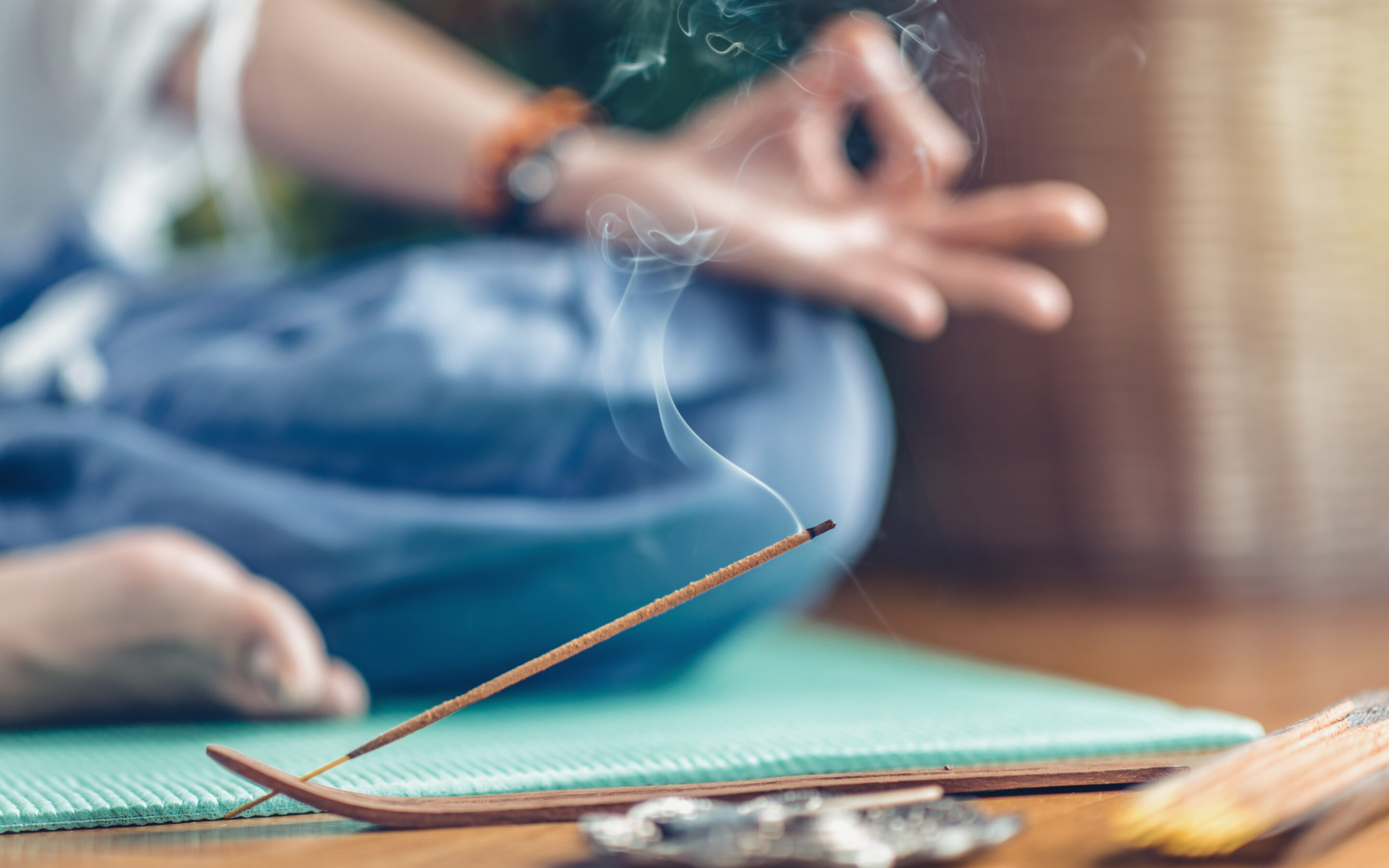 Woman enjoying her ritual of meditation with focus on burning incense stick