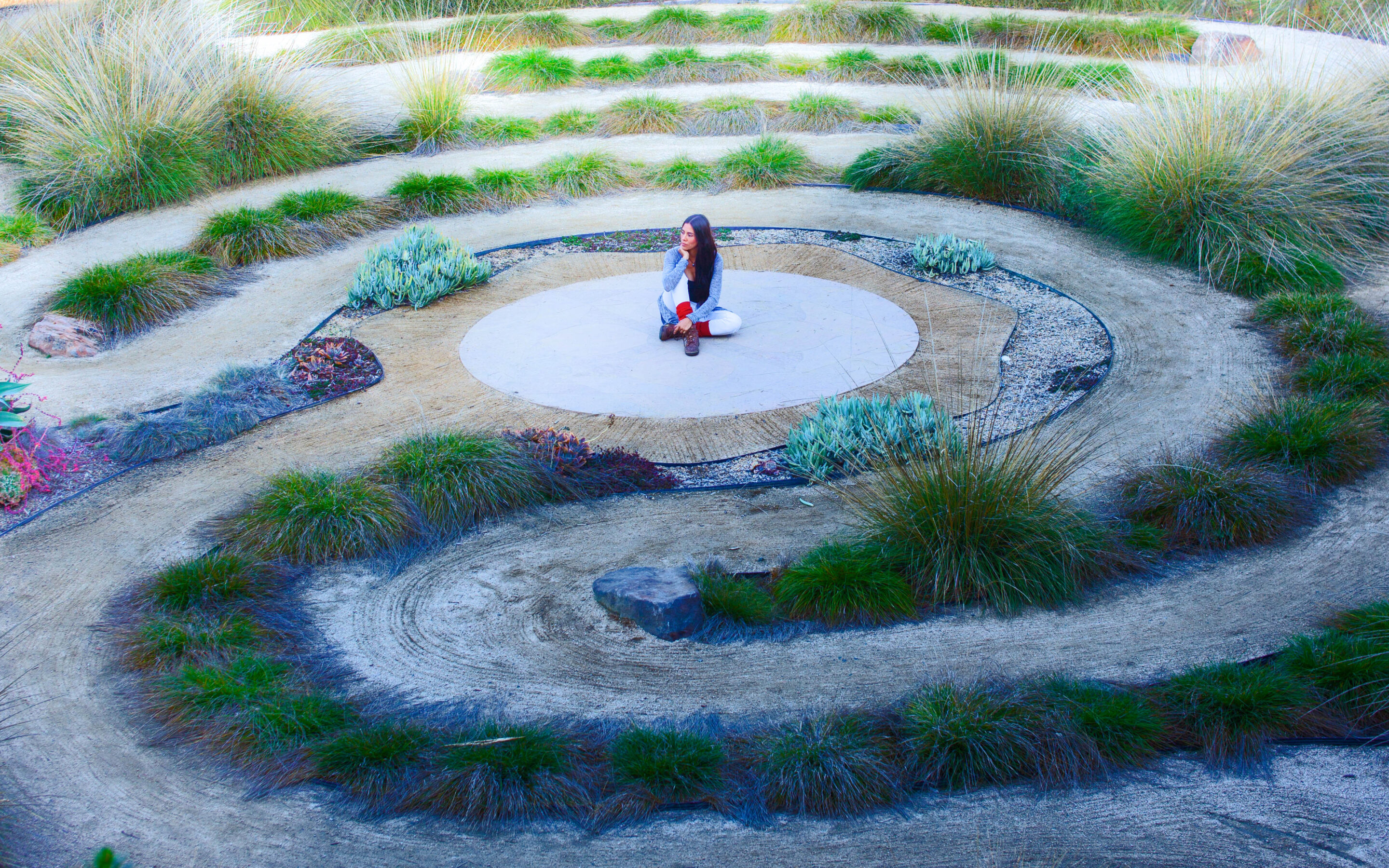 Woman sitting in the middle of a labyrinth