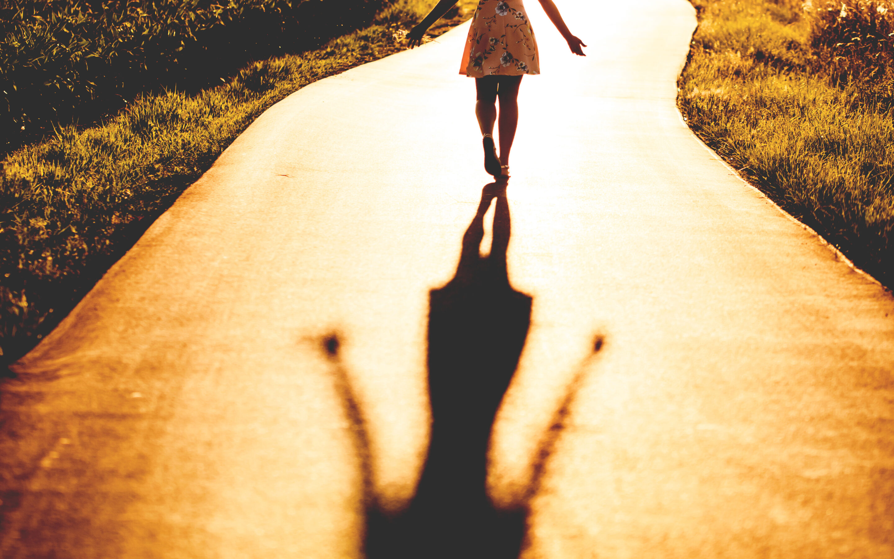 Woman walking towards light with her shadow
